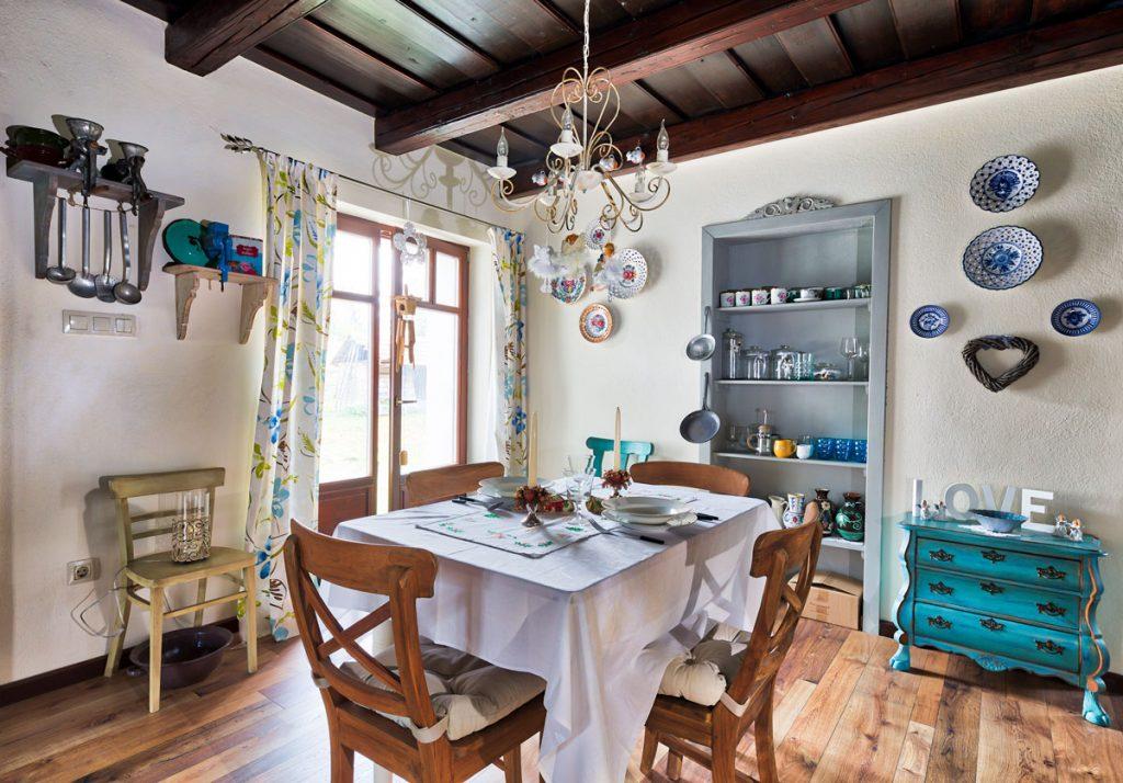 vidiecka kuchyňa so zabudovanými policami v stene, s dreveným nábytkom a priznaným dreveným stropom