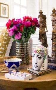 zátišie na stolíku pozostávajúce zo vzorovanej vázy s kvetmi, vzorovanej misky a keramickej nádoby s poklopom a orientálnych drevených vyrezávaných sošiek
