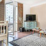 obývačka s vintage tyrkysovou komodou pod telkou a kobercom s geometrickým vzorom