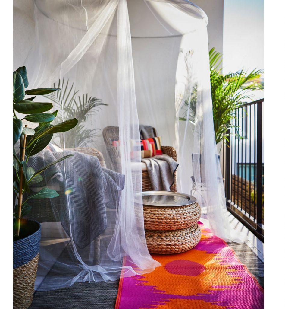 sedenie na terase z prírodných materiálov pod bielym záclonovým baldachýnom