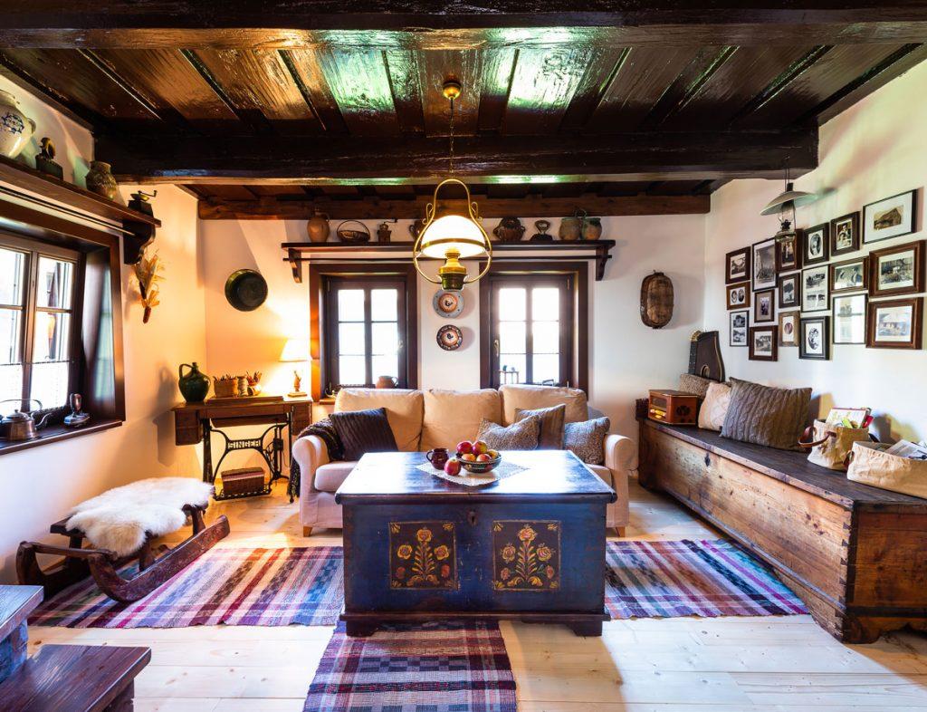vidiecka obývačka s farebnou truhlicou, lakovaným dreveným stropom, so starodávnym šijacím strojom ako stolíkom a truhlicou na odkladanie vecí