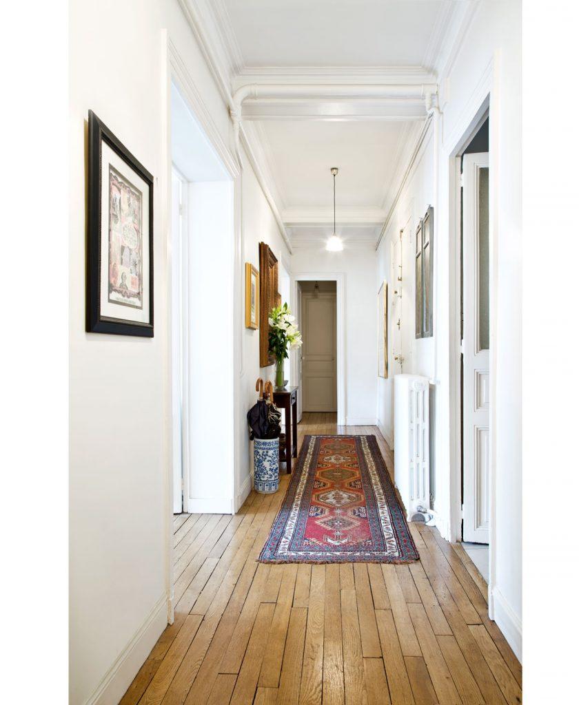 Dlhá úzka chodba v historickom byte s orientálnym kobercom a drevenými parketami.