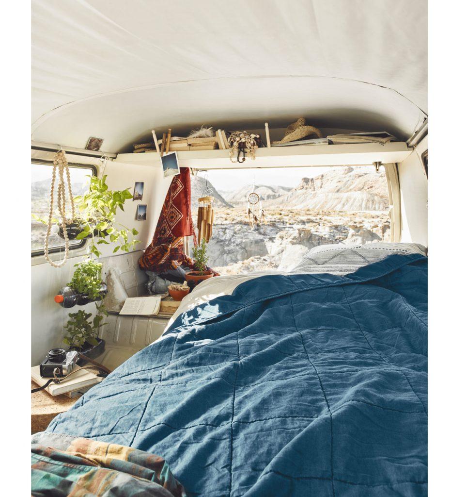 posteľ v karavane, na ktorej je modrý prešívaný prehoz