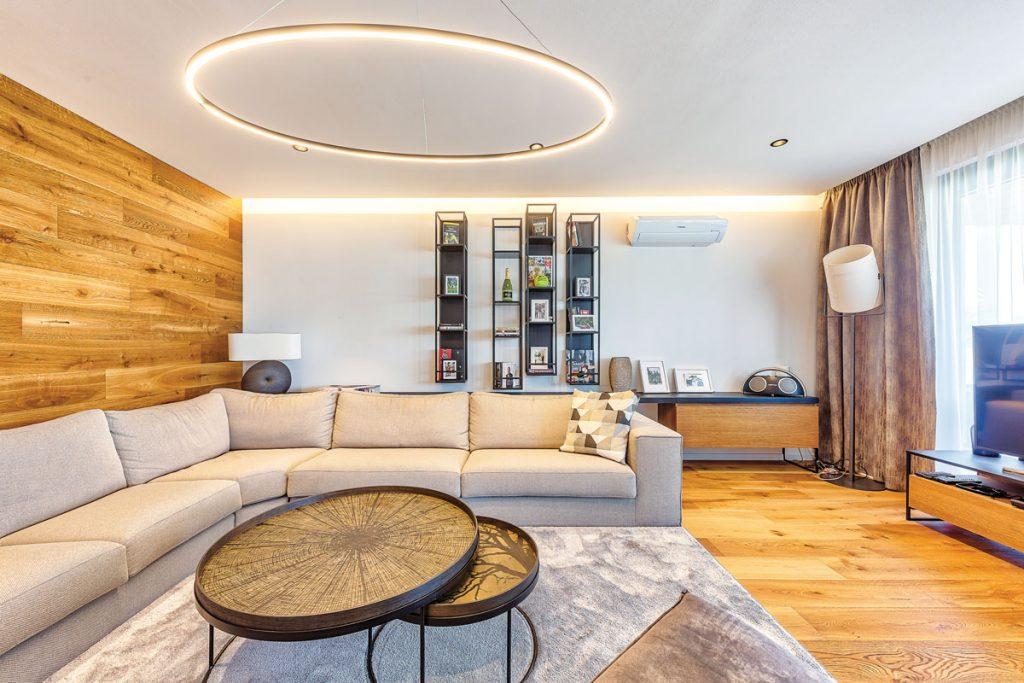 retro interiér obývačky s kruhovým svietidlom a kruhovým stolíkom a s dreveným obkladom na stene