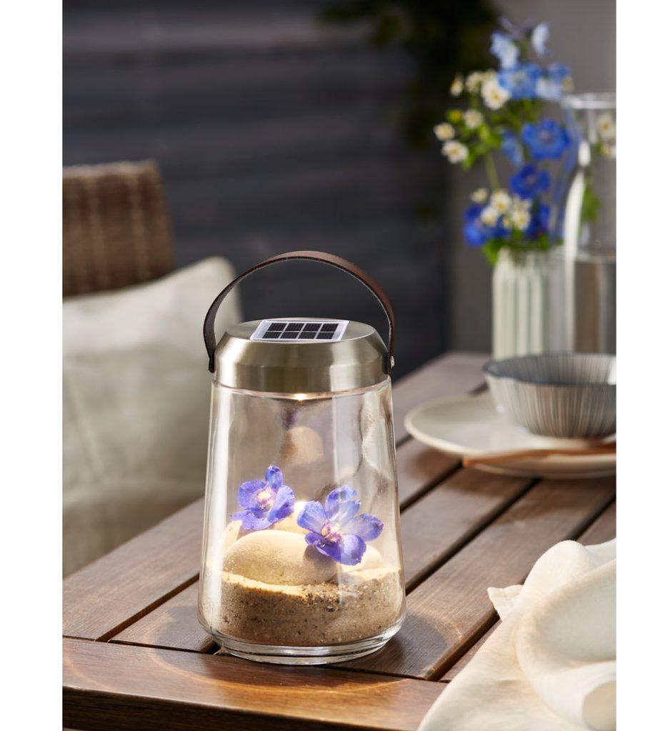 sklenená solárna lampa s pieskom, kamienkami a kvetinami vnútri