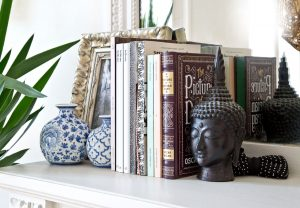 polica s knihami, dekoráciou hlavy Budhu a keramickými vázami s modrými ázijskými vzormi
