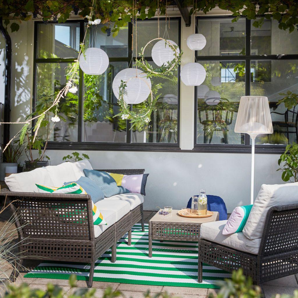 terasové sedenie z prírodných materiálov s pruhovaným kobercom a závesnými papierovými lampiónmi na solárny pohon