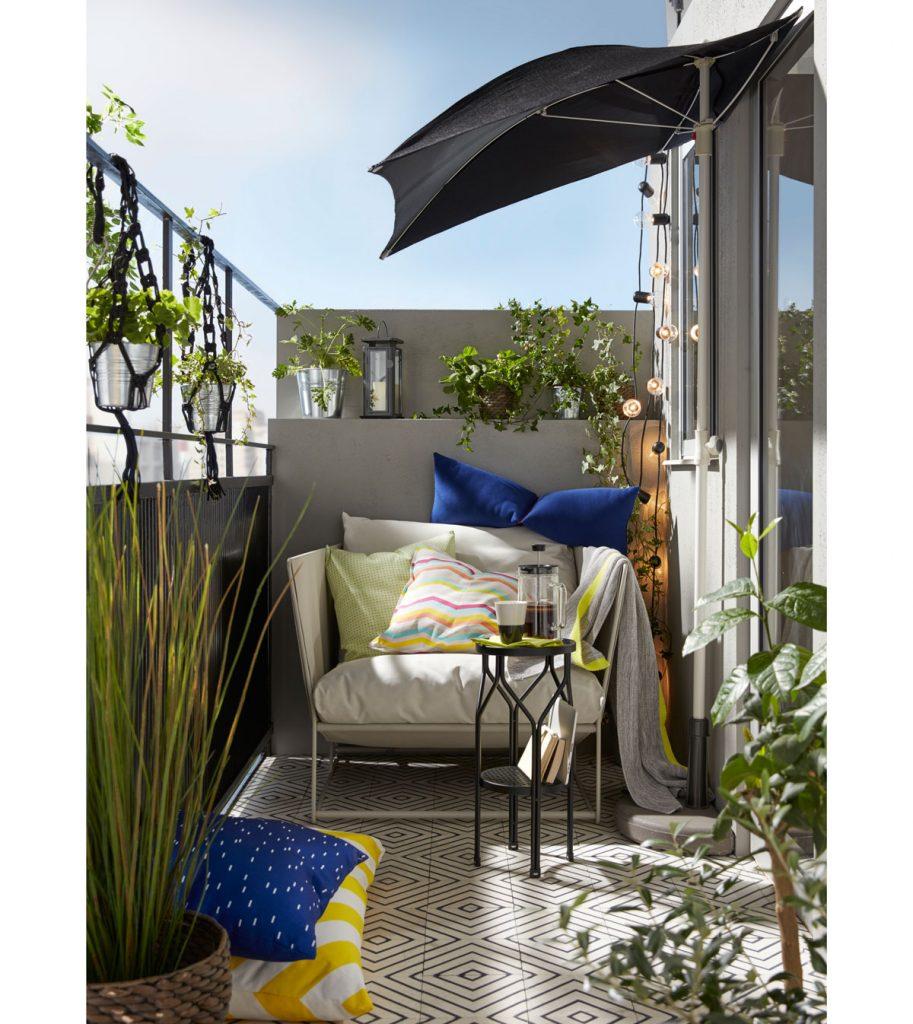 balkón s kreslom, vankúšmi a dekou, svetelnými reťazami a slnečníkom