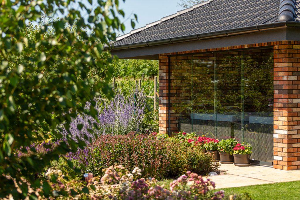 záhrada s vonkajšou kuchyňou, vedľa ktorej rastú záhony trvaliek a cibuľovín a dreviny