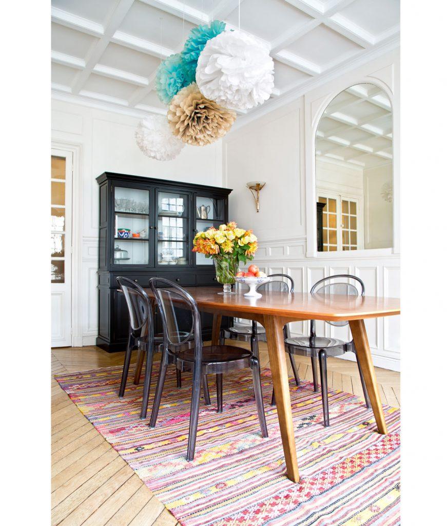 Jedáleň s drevenými parketami, vysokými stropmi a dvojkrídlovými dverami, zariadená s čiernym príborníkom, retro dreveným stolom a priesvitnými plastovými dizajnérskymi stoličkami, na zemi je pestrofarebný ručne viazaný koberec v etno štýle.