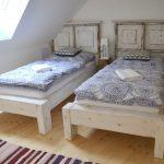 jednolôžkové biele postele z recyklovaného dreva prispôsobené šikmej stene v podkroví