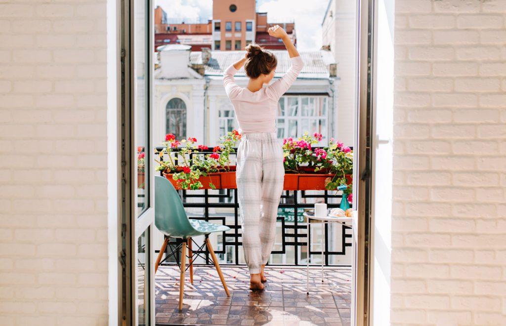 žena stojaca na balkóne, ktorý je zariadený s modrou stoličkou, okrúhlym stolíkom a kvetmi