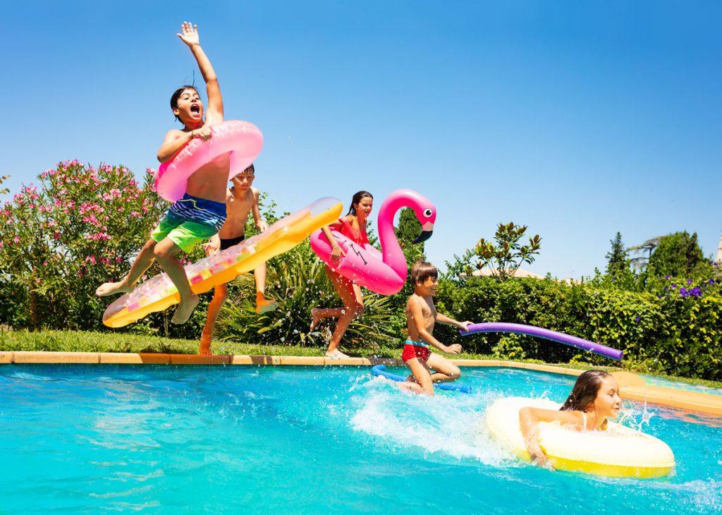 deti skákajúce do bazénu