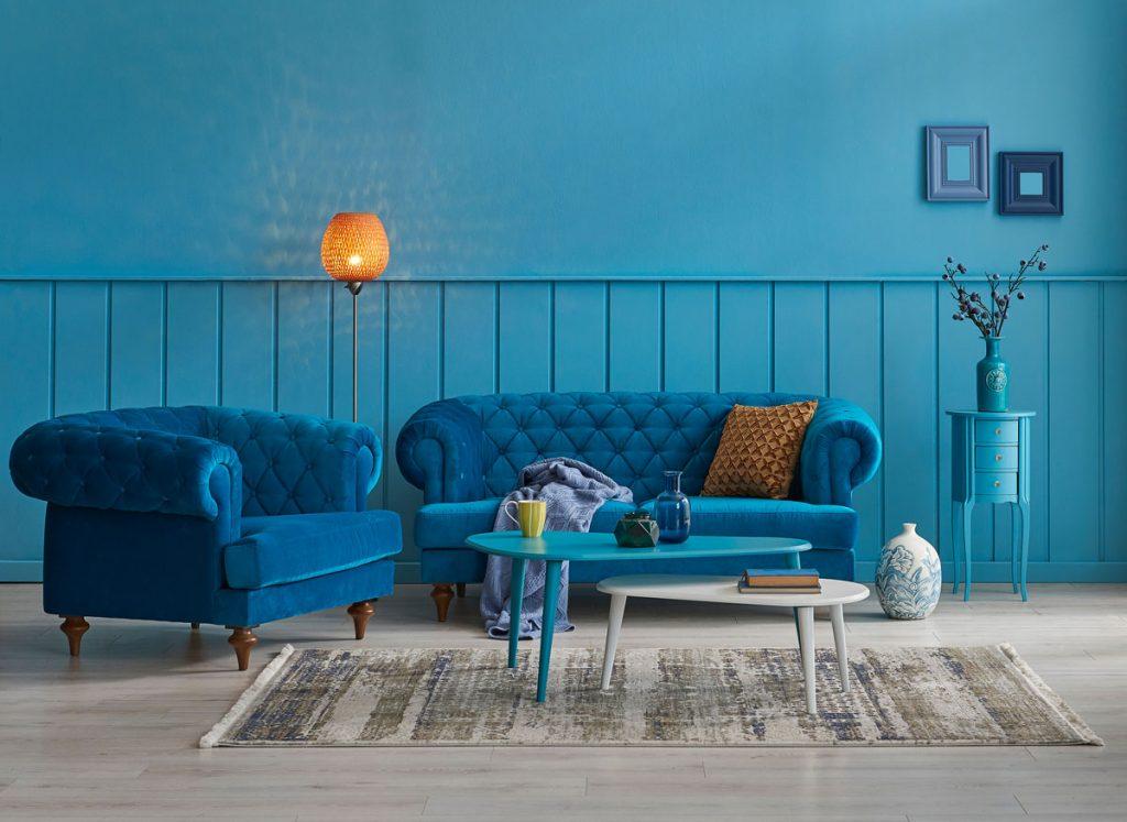 interiér so sedačkou, kreslom a stolíkmi, ladený do modrých farieb