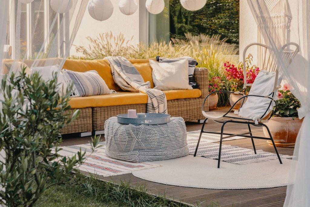 terasa s ratanovým nábytkom, pleteným pufom, kobercami a vankúšmi