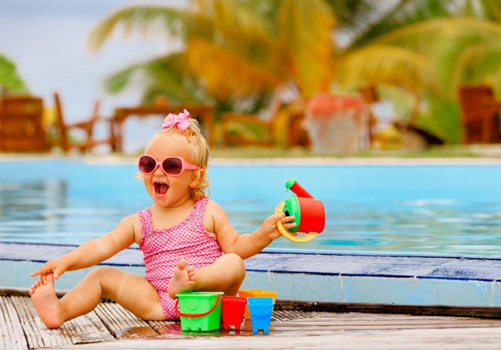 malé dieťa sa hrá s hračkami pri bazéne