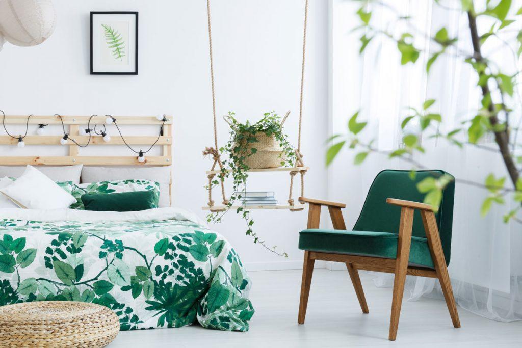 Interiér v tropickom štýle s naturálnymi prvkami. Súčasťou interiéru je zelené zamatové kreslo, paletová posteľ s motívmi listov na posteľnom prádle, pletený prírodný sedák a pletený obal s kvetináčom položeným na závesnej polici.