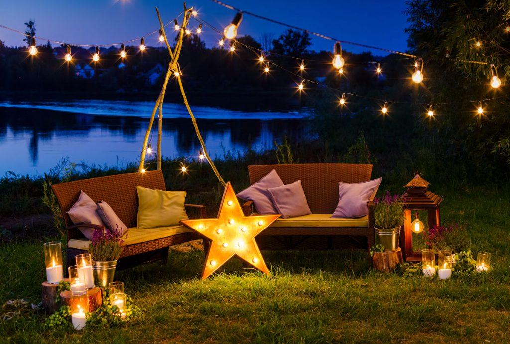 osvetlené záhradné sedenie pomocou reťazových svetiel a rôznych lampášov
