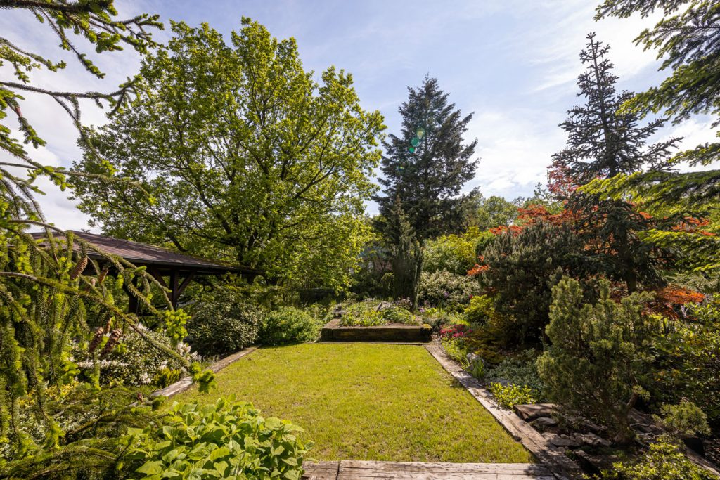 prírodná záhrada s plochou trávnika, altánkom a záhonmi s drevinami a trvalkami