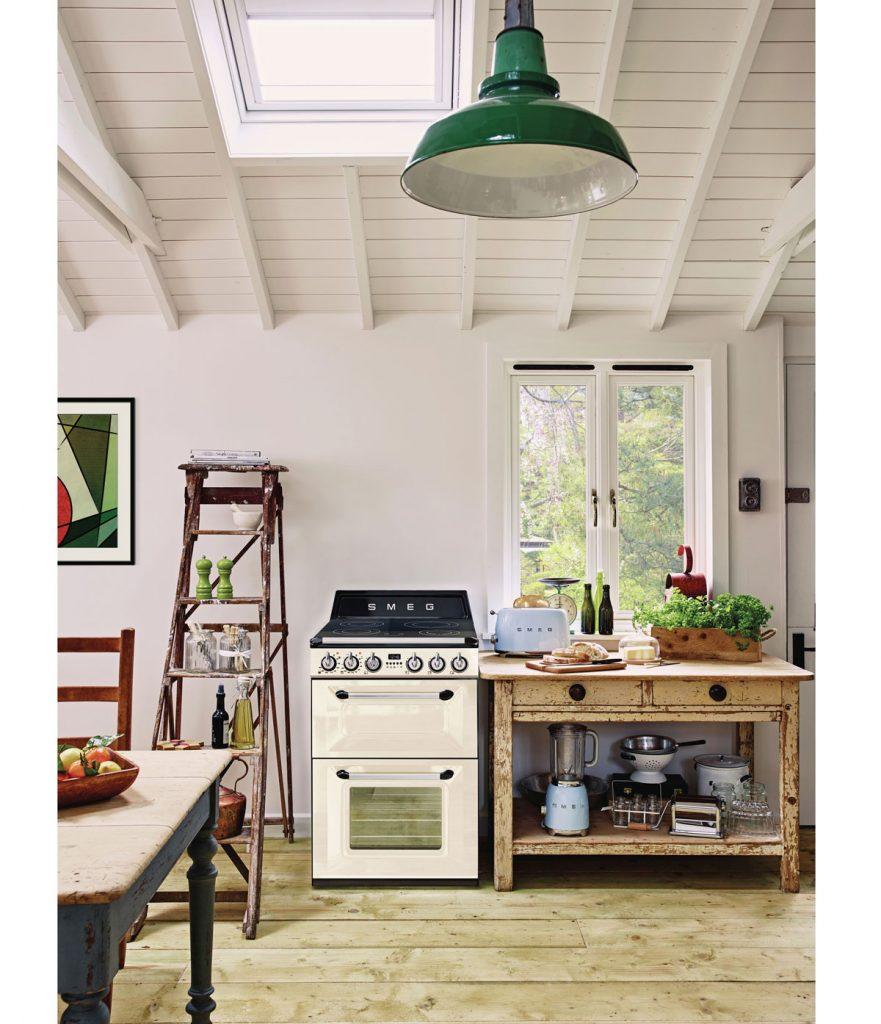retro kuchyňa s recyklovaným nábytkom v podobe rebríka, ktorý slúži na odkladanie vecí a stola so zásuvkami, na ktorom sú poukladané riady a spotrebiče