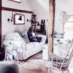 vidiecka obývačka v škandinávskom štýle s dreveným trámom uprostred miestnosti, s bielou pohovkou, bielou truhlicou ako stolíkom, bielym hojdacím kreslom a kravskou kožou na zemi