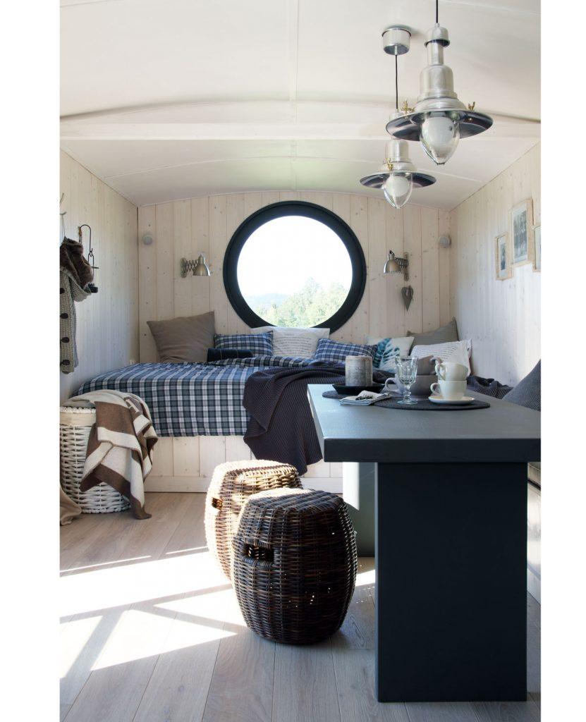 interiér víkendovej maringotky s okrúhlym oknom zariadený v kombinácii vidieckeho a severského štýlu