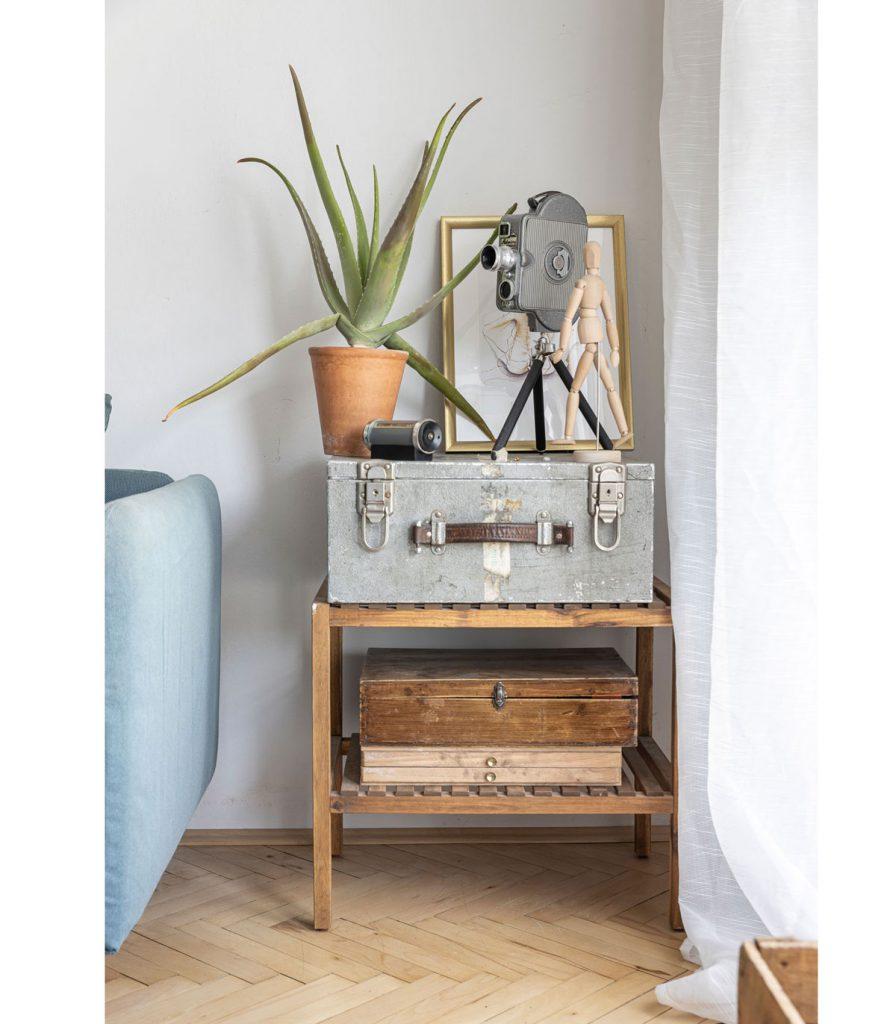 otvorený stolík so starožitnými kuframi a starožitnou kamerou v interiéri so zachovalými parketami