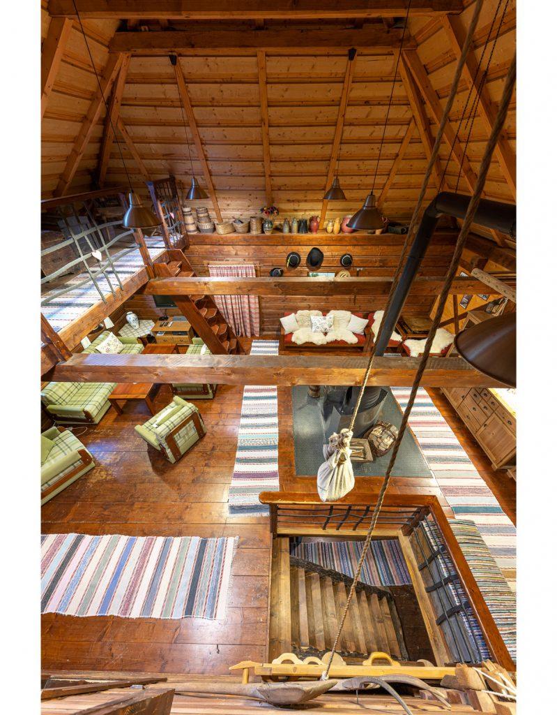 pohľad na obývaciu časť v drevenici, s drevenou podlahou, tkanými pokrovcami, dreveným nábytkom a pieckou