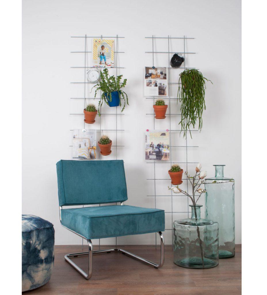 interiér s modrým kreslom a drôtenými stojanmi, na ktorých visia obrázky a kvetiny