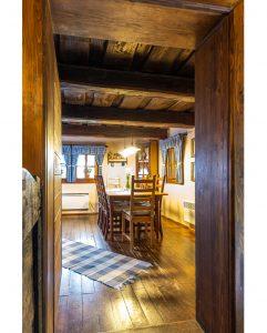 kuchyňa v drevenici s dreveným stolom a stoličkami a károvanými modrými závesmi