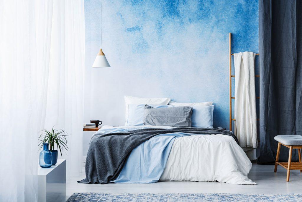 spálňa ladená do modrých odtieňov s rozpíjanou modrou stenou so vzhľadom akvarelu