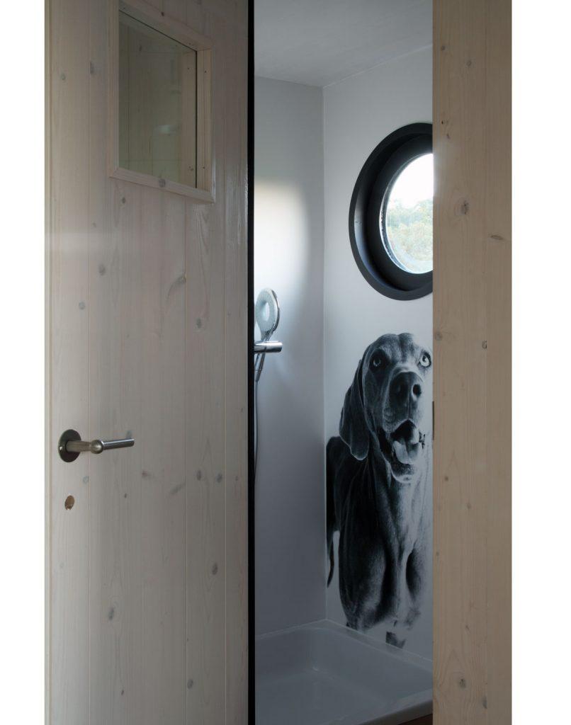 kúpeľňa v maringotke so sprchovacím kútom a kruhovým oknom