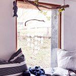časť interiéru v škandinávskom štýle s pohľadom na okno s dekoráciou z naplaveného dreva