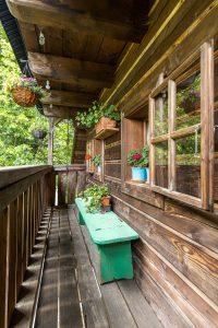 pavlač na tradičnej drevenici so zelenou lavičkou a kvetinami
