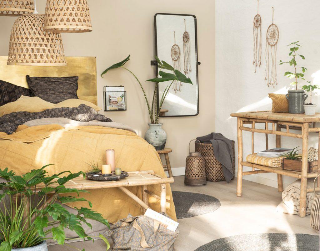 Spálňa v prírodnom štýle ladená do odtieňov hnedej a žltej. Na posteli je žlté posteľné prádlo a nábytok je tvorený z bambusového stola a menšieho stolíka pri posteli, nechýbajú kvetiny a pletené dekorácie.