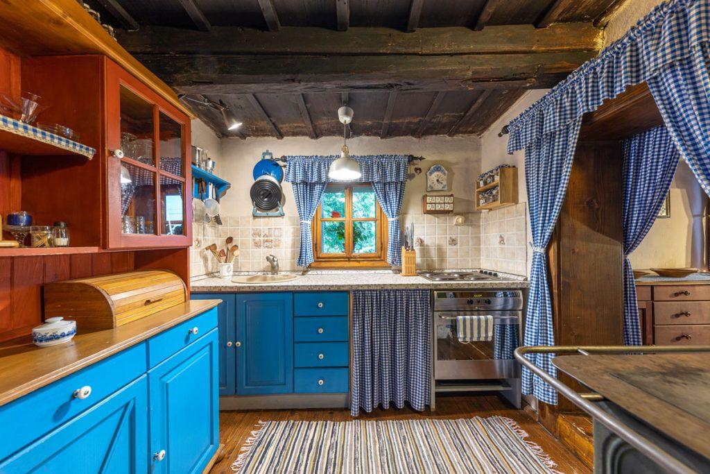 modrá kuchynská zostava s modrými károvanými závesmi v tradičnej drevenici