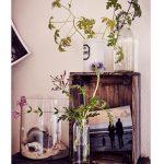 stolík s dekoráciami v podobe sklenenej nádoby s mušľami, sklenenej vázy s kvetinami a starej drevenej debničky slúžiacej ako skrinka