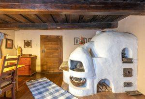 murovaná pec v drevenici, ktorá slúži aj na spanie