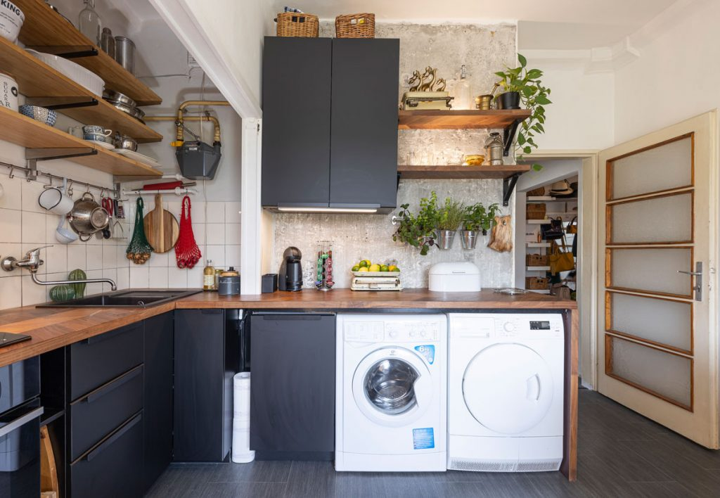 čierna kuchyňa v rustikálnom štýle s otvorenými drevenými policami, práčkou a sušičkou