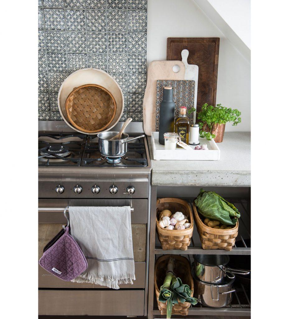 úložné kuchynské priestory pozostávajúce z košíkov na zeleninu v otvorenej skrinke a podnosu na kuchynskej linke, na ktorom sú poukladané rôzne drobnosti