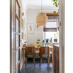 jedálenský kút v retro štýle s drevenými stoličkami a stolom, pleteným lustrom a autorskými obrazmi