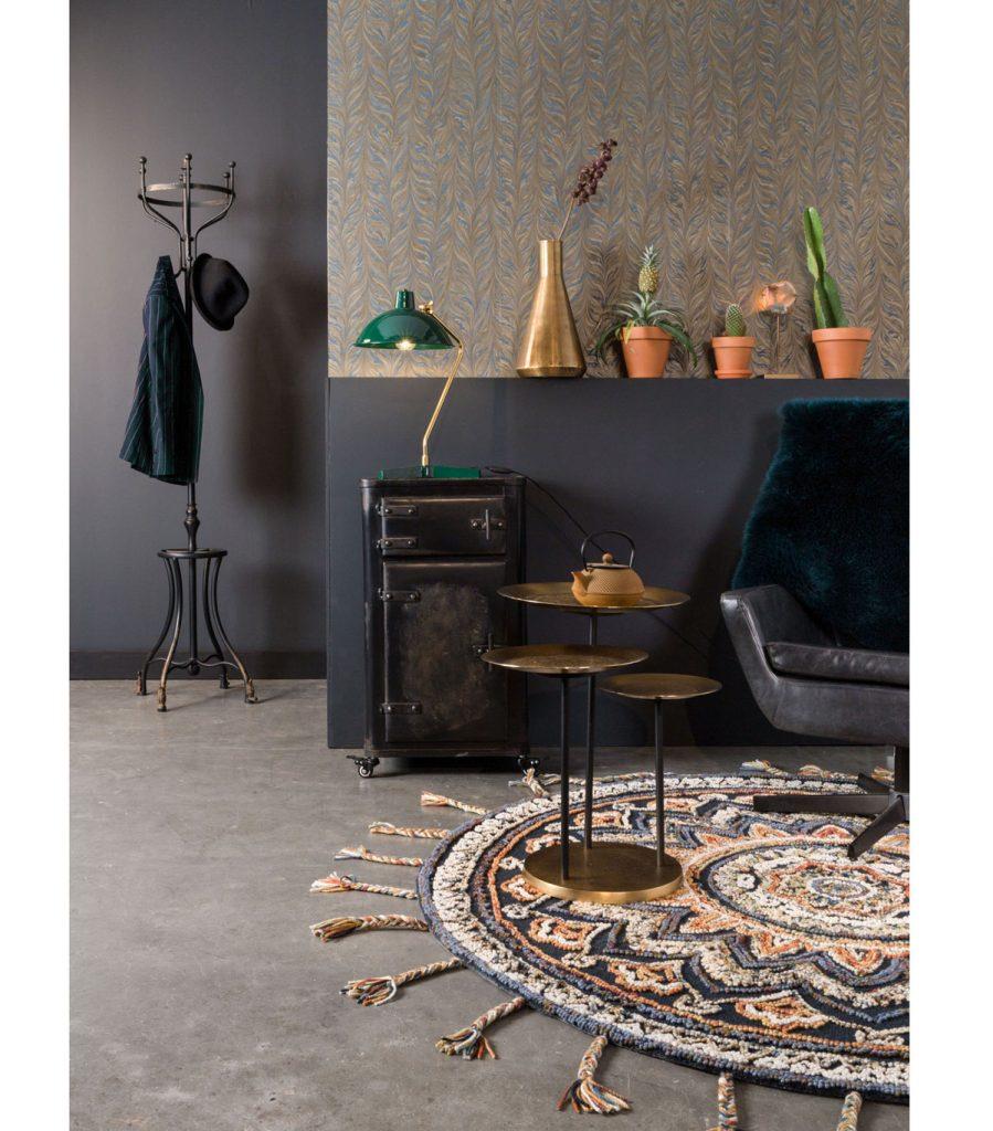 elegantný interiér s koženým otočným kreslom, okrúhlym kobercom a pieckou, ktorá slúži ako stolík pre retro lampu