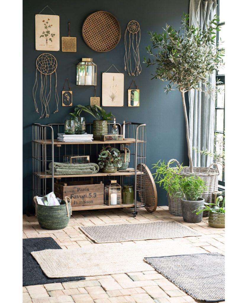 prírodne ladený interiér s kovovým policovým vozíkom, nad ktorým sú zavesené obrázky a pletené dekorácie