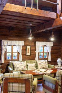 obývačka v drevenici zariadená drevenou sedacou súpravou so zeleným károvaným poťahom
