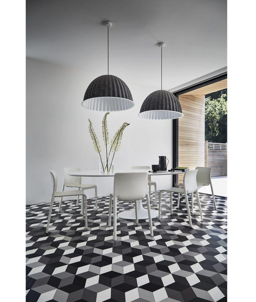 jedáleň v bielosivých tónoch s bielym oválnym stolom a stoličkami, tmavými svietidlami a podlahou s kockovaným 3D efektom