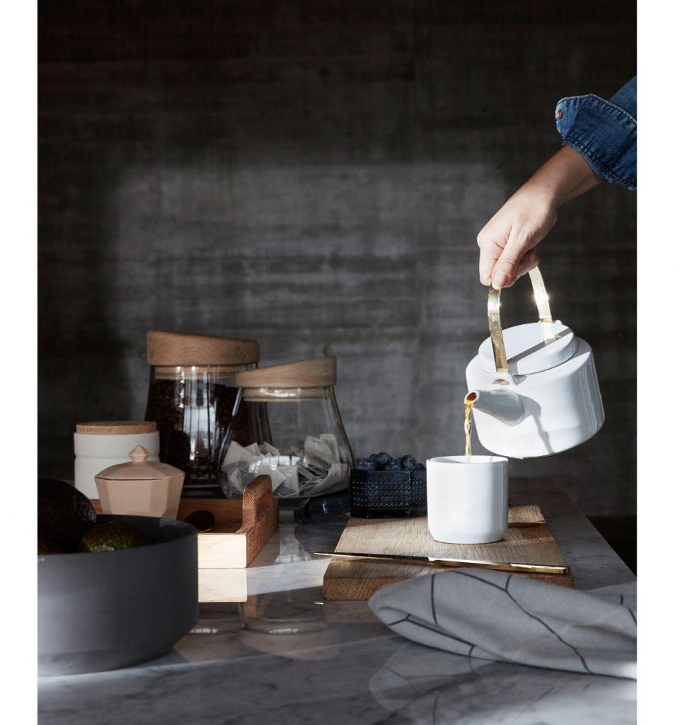jednoduchá biela čajová kanvica s hrnčekom a sklenené dózy s drevenými uzávermi
