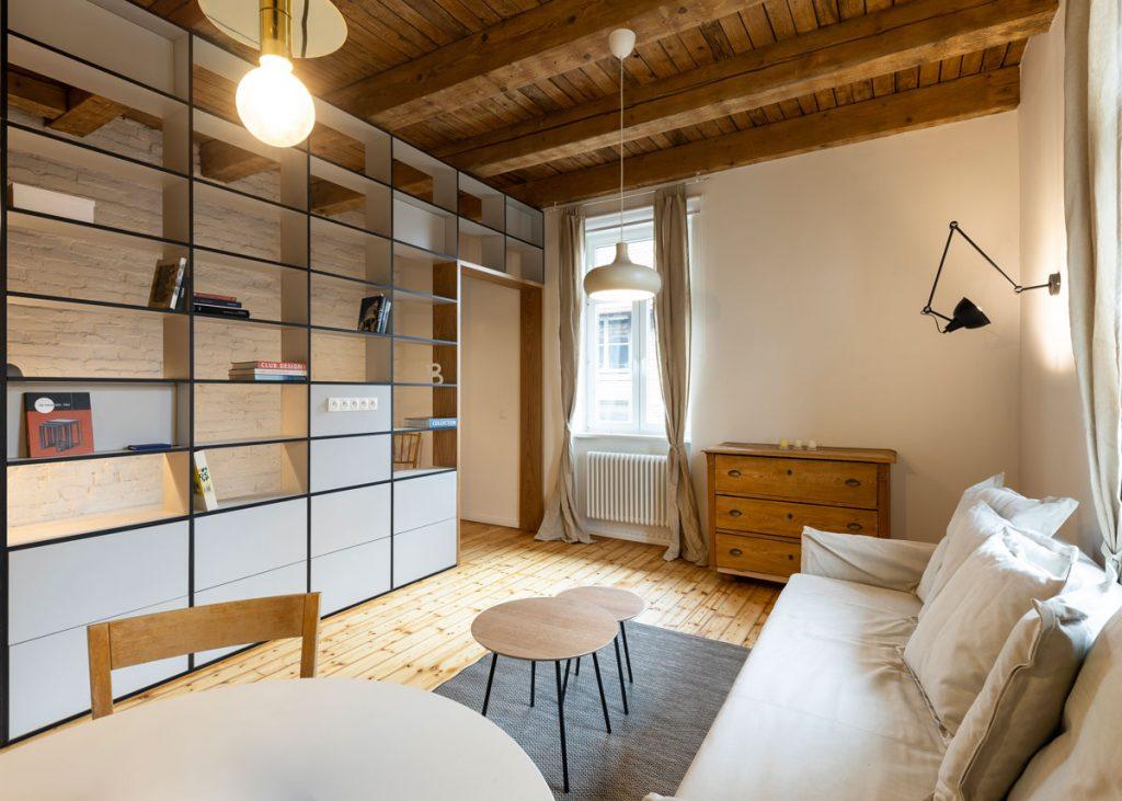 obývačka v jednoizbovom byte predelená policovým systémom od spálne, zariadená dreveným nábytkom a pohovkou v prírodných farbách