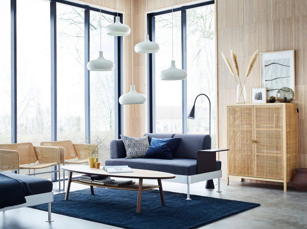 interiér v minimalistickom japandi štýle s drevenými obkladmi, s modrou jednoduchou sedačkou, modrým kobercom, oválnym stolíkom a prírodnou vypletanou skriňou