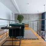 poschodie v mezonetovom byte so zelenou pohovkou a kovovým industriálnym stolíkom