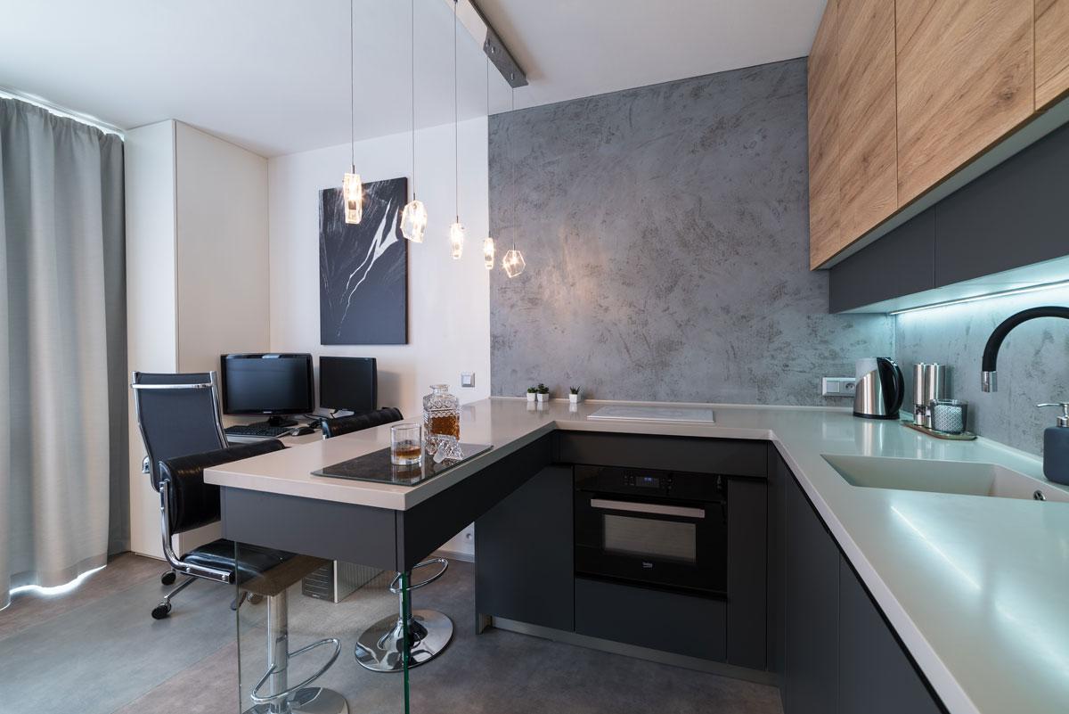 moderná minimalistická kuchyňa v garsónke s jedálenským pultom a kuchynskou zostavou v odtieňoch šedej